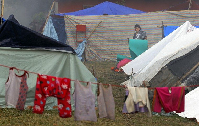 A Nepalese woman cleans out her makeshift tent in Kathmandu, Nepal. The international response has been slow to an appeal for emergency funds to help the millions of people hit by last month's earthquake in Nepal. The international response has been slow to an appeal for emergency funds to help the millions of people hit by last month's earthquake in Nepal, a U.N. official said. (Niranjan Shrestha/Associated Press)