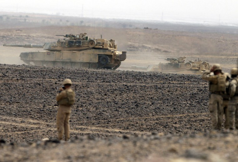 "Soldiers watch tanks advancing as they take part in joint Jordan-US maneuvers during the ""Eager Lion"" military exercises in Mudawwara, near the border with Saudi Arabia, some 280 kilometres south of the Jordanian capital, Amman, on May 18, 2015. The annual ""Eager Lion"" exercises includes the participation of 10,000 troops from at least 18 countries, and incorporates scenarios including disaster relief and air defense. (KHALIL MAZRAAWI/AFP/Getty Images)"