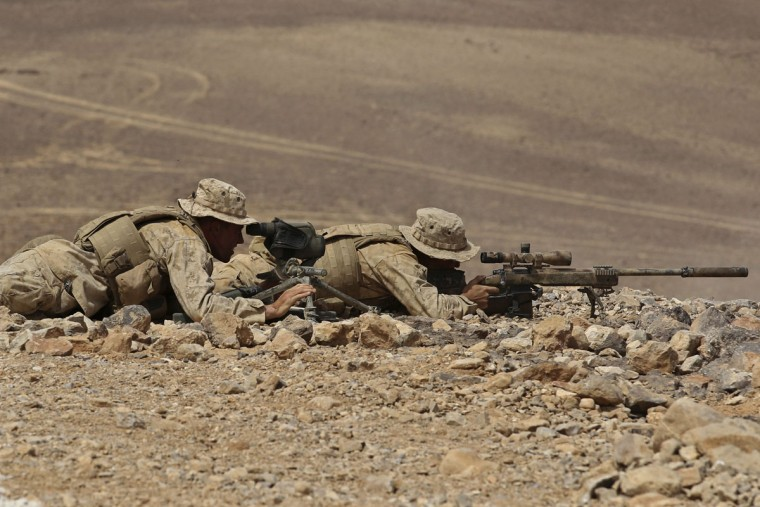 "A U.S. sniper team performs in a shooting drill during 18-nation military exercises in a field near the border with Saudi Arabia, in Mudawara, 280 kilometers (174 miles) south of Amman, Jordan, Monday, May 18, 2015. Some 10,000 troops took part in the two-week ""Eager Lion"" exercises hosted by Jordan for the fifth year. (AP Photo/Raad Adayleh)"