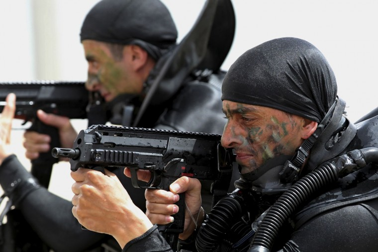 """Jordanian forces practice a drill to free a ship seized by mock terrorists during 18-nation military exercises off Aqaba's seaport, 330 kilometers (205 miles) south of Amman, Jordan, Monday, May 18, 2015. Some 10,000 troops took part in the two-week """"Eager Lion"""" exercises hosted by Jordan for the fifth year. (AP Photo/Raad Adayleh)"""