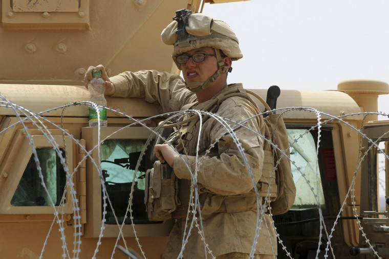 """A U.S. soldier takes a break during 18-nation military exercises in a field near the border with Saudi Arabia, in Mudawara, 280 kilometers (174 miles) south of Amman, Jordan, Monday, May 18, 2015. Some 10,000 troops took part in the two-week """"Eager Lion"""" exercises hosted by Jordan for the fifth year. (AP Photo/Raad Adayleh)"""