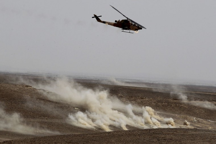 "A Jordanian helicopter fires during 18-nation military exercises in a field near the border with Saudi Arabia, in Mudawara, 280 kilometers (174 miles) south of Amman, Jordan, Monday, May 18, 2015. Some 10,000 troops took part in the two-week ""Eager Lion"" exercises hosted by Jordan for the fifth year. (AP Photo/Raad Adayleh)"