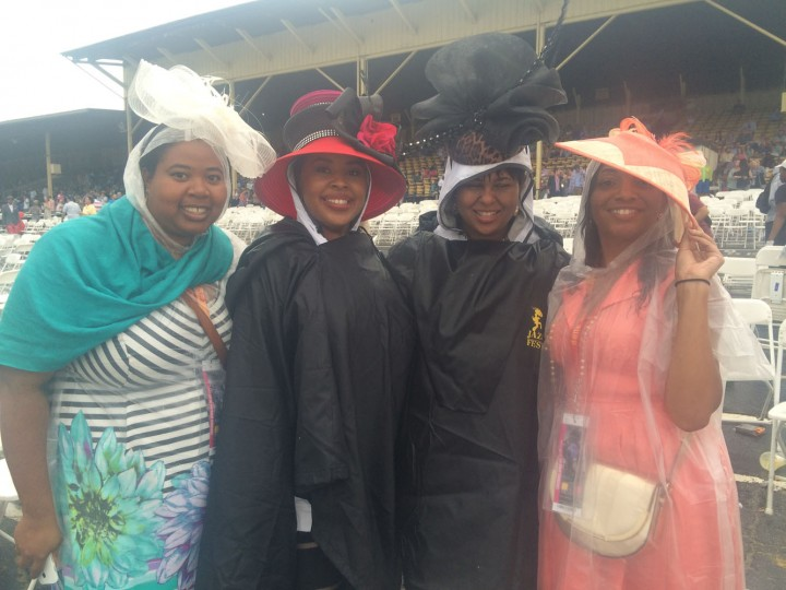 "These ladies topped plastic ponchos with eye-catching hats to keep their style intact while watching a rain-soaked race. ""We came out and we were like, hey, that's the race we want to see,"" said Enjoli Nelson, 36, of Houston (second from left). They had money on American Pharoah, which sweetened the victory, and plan to stick around for the last race of the day. Left to right, Sharita Cooper, 29, of Washington; Nelson; Erica Williams, 28, of Bowie; and Shontae Hewlett, 36, of New Orleans, ""where we're not afraid of rain."" (Quinn Kelley/Baltimore Sun)"