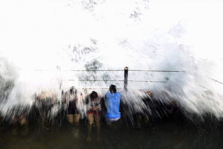 People defy large waves on the San Blas beach, on April 19, 2015 in La Libertad, 34 km south of San Salvador. (Marvin RECINOS/AFP/Getty Images)