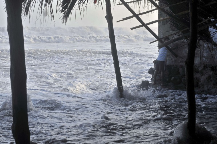 A man tries to protect himself during a strong ocean swell in La Libertad, 34 km south of San Salvador, on May 3, 2015. (Marvin RECINOS/AFP/Getty Images)