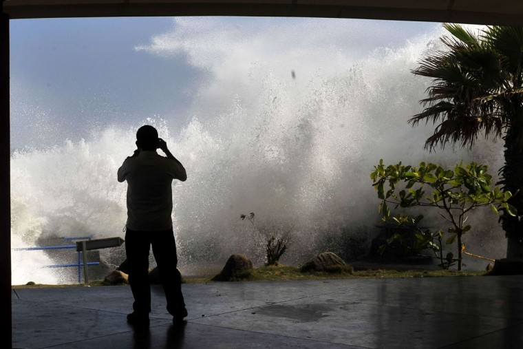 A man takes a picture of the waves in La Libertad, 34 km south of San Salvador, on May 3, 2015. (Marvin RECINOS/AFP/Getty Images)