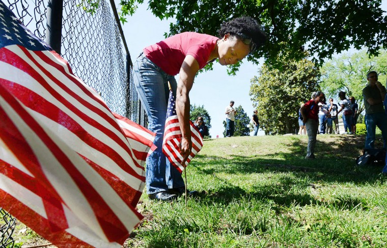 Tonica Johnson places a flag during the Memorial Day Historic Fitzgerald Family cemetery ceremony, at the Maplewood Cemetery in Durham, N.C., Monday, May 25, 2015. (Bernard Thomas/The Herald-Sun via AP)