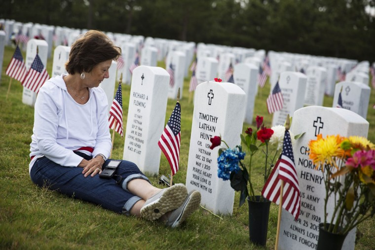 "Vickie Hunt sits next to the grave of her late husband, Vietnam veteran U.S. Marine Cpl. Timothy Hunt, at Georgia National Cemetery on Memorial Day, Monday, May 25, 2015, in Canton, Ga. ""I come every Memorial Day,"" says Hunt. ""As soon as I go through the gates here it brings me a sense of peace."" (AP Photo/David Goldman)"