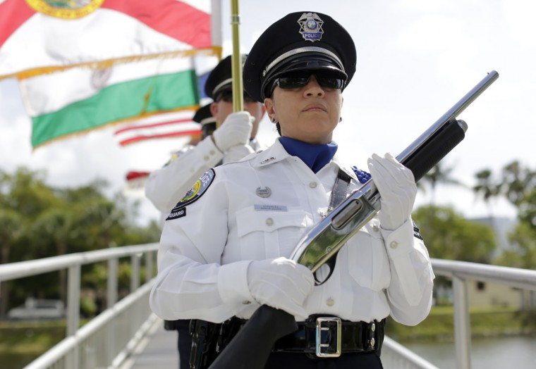 A North Miami Beach police honor guard marches during a Memorial Day event in honor of veterans who died in service to the country, Monday, May 25, 2015, in North Miami Beach, Fla. (AP Photo/Lynne Sladky)