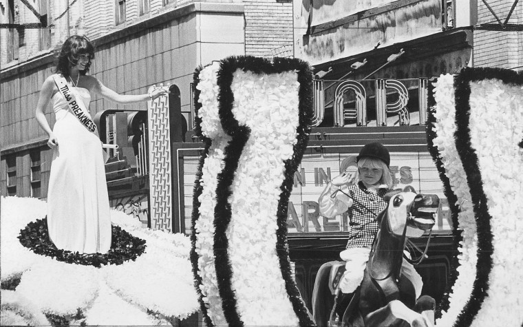 Miss Preakness, Susan Rosenberg, waves to bystanders as a miniature jockey follows suit from a parade float as Preakness Week festivities got under way over the weekend for the1977 Preakness. (Baltimore Sun file photo)