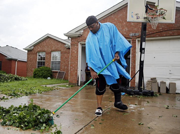 George Young sweeps leaves from a driveway at the Bent Creek Estates subdivision following a storm in Denton, Texas, Sunday, May 10, 2015. Several Great Plains and Midwest states were in the path of severe weather, including in North Texas, where the National Weather Service said a likely tornado damaged roofs and trees near Denton. (G.J. McCarthy/The Dallas Morning News via AP)