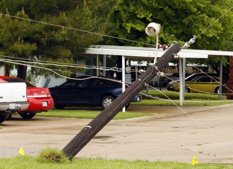 A power pole leans along Fort Worth Avenue after a storm in Denton, Texas, Sunday, May 10, 2015. Several Great Plains and Midwest states were in the path of severe weather, including in North Texas, where the National Weather Service said a likely tornado damaged roofs and trees near Denton. (Richard W. Rodriguez/The Fort Worth Star-Telegram via AP)