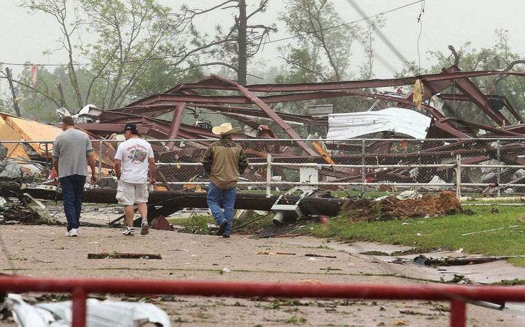 Residents survey damage to an elementary school caused by severe weather, Monday, May 11, 2015, in Van, Texas. About 30 percent of the community was damaged from the storm late Sunday, according to Chuck Allen, fire marshal and emergency management coordinator for Van Zandt County. (AP Photo/Todd Yates)