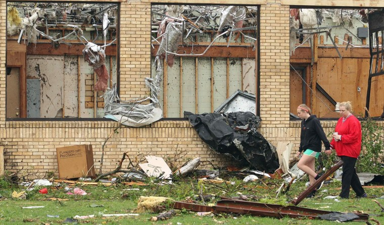 Grace Santo, 14, holds hands with her mother, Vista, right, as they survey severe weather damage at an elementary school, Monday, May 11, 2015, in Van, Texas. About 30 percent of the community was damaged from the storm late Sunday, according to Chuck Allen, fire marshal and emergency management coordinator for Van Zandt County. (AP Photo/Todd Yates)