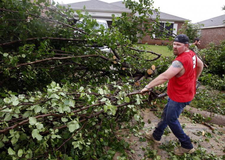 Jason Olsen clears a downed tree blocking his driveway after a possible tornado touched down in his neighborhood in Denton, Texas, Sunday, May 10, 2015. (Richard W. Rodriguez/The Fort Worth Star-Telegram via AP)