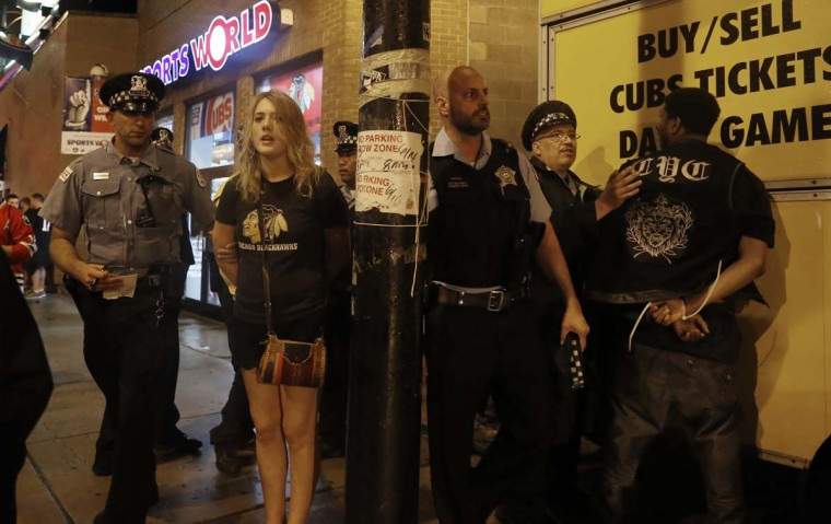 Chicago Blackhawks fans are arrested by Chicago police officers on Addison Street in the Wrigleyville neighborhood after the Chicago Blackhawks won the Stanley Cup, defeating the Tampa Bay Lightning Monday, June 15, 2015 in Chicago. (AP Photo/Christian K. Lee)