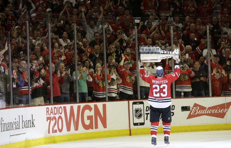 Fans cheer as Chicago Blackhawksí Kris Versteeg skates around the ice with the Stanley Cup Trophy after defeating the Tampa Bay Lightning in Game 6 of the NHL hockey Stanley Cup Final series on Monday, June 15, 2015, in Chicago. The Blackhawks defeated the Lightning 2-0 to win the series 4-2. (AP Photo/Nam Y. Huh)