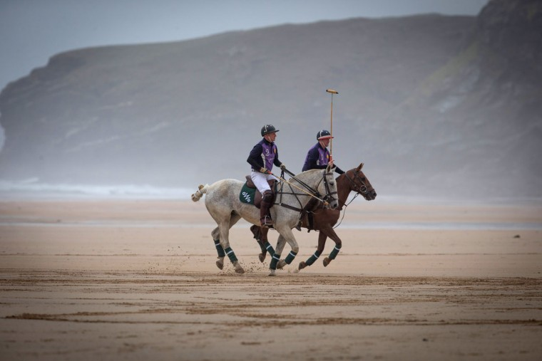 Polo players Andy Burgess (wearing the No. 2 shirt) riding Tonka and Daniel Loe (wearing the No. 1 shirt) and riding brown horse La Sophia practice for the annual beach polo competition being held on the beach at Watergate Bay, near Newquay in Cornwall, England. (Photo by Matt Cardy/Getty Images)