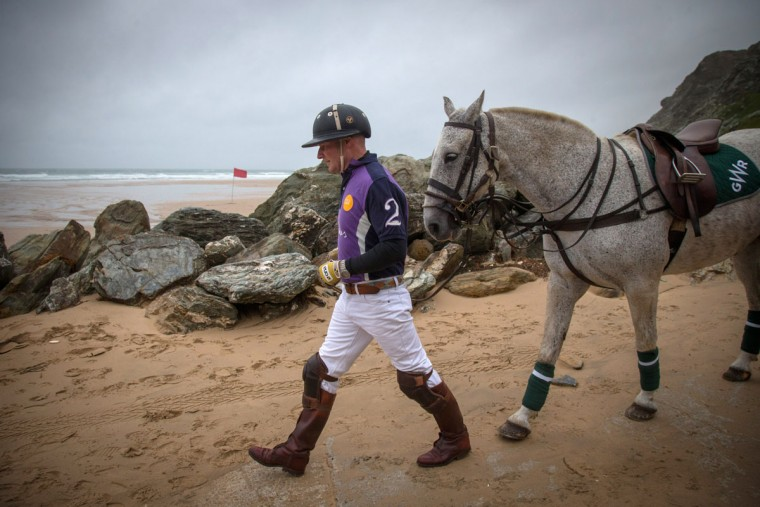 Polo player Andy Burgess leads Tonka to practice for the annual beach polo competition being held on the beach at Watergate Bay, near Newquay later this month on June 2, 2015 in Cornwall, England. (Photo by Matt Cardy/Getty Images)