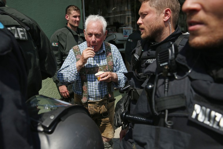 An elderly man wearing Lederhosen eats ice-cream as riot police walk past during a march by anti-G7 protesters through the city center the day before the summit of G7 leaders on June 6, 2015 in Garmisch-Partenkirchen, Germany. G7 leaders will meet at nearby Schloss Elmau on June 7-8 and protesters are holding a variety of gatherings and demonstrations to voice their opposition. (Photo by Sean Gallup/Getty Images)