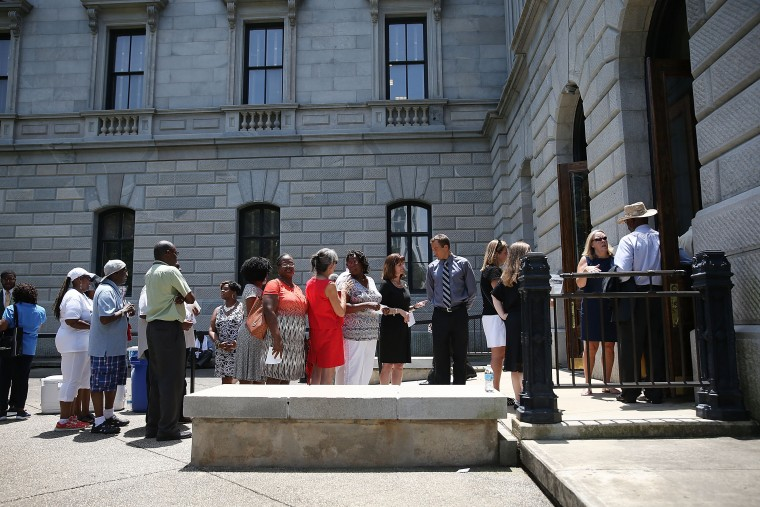 COLUMBIA, SC - JUNE 24: People wait in a long line to enter the Capitol building to pay their respects to church pastor and South Carolina State Sen. Clementa Pinckney who will lie in repose at the Statehouse Rotunda on June 24, 2015 in Columbia, South Carolina. Pinckney was one of nine people killed during a Bible study inside Emanuel AME church in Charleston. U.S. President Barack Obama and Vice President Joe Biden are expected to attend the funeral which is set for Friday June 26 at the TD Arena. (Photo by Joe Raedle/Getty Images)