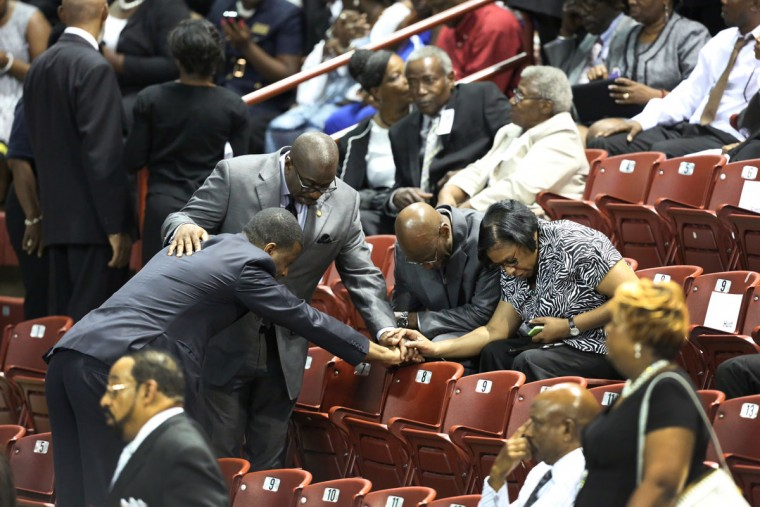 Mourners pray as thousands begin to fill the College Charleston TD Arena on June 26, 2015, in Charleston, South Carolina. President Barack Obama will deliver the eulogy for one of the victims, Sen. Clementa Pinckney, during his funeral Friday at TD Arena. Suspected shooter Dylann Roof, 21 years old, is accused of killing nine people on June 17th during a prayer meeting in the church, which is one of the nation's oldest black churches in Charleston. (Photo by Grace Beahm-Pool/Getty Images)