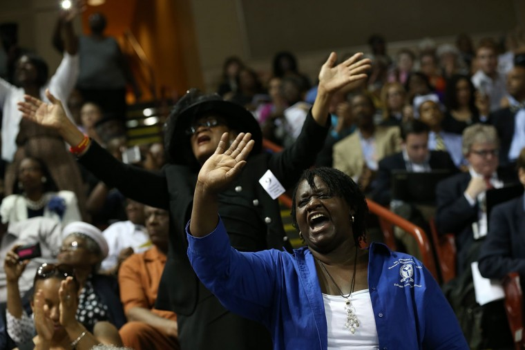 Mourners sing gospel hymns during the funeral service where U.S. President Barack Obama will deliver the eulogy for South Carolina State senator and Rev. Clementa Pinckney who was killed along with eight others in a mass shooting June 26, 2015 in Charleston, South Carolina. Suspected shooter Dylann Roof, 21, is accused of killing nine people on June 17th during a prayer meeting in the church, which is one of the nation's oldest black churches in Charleston. (Photo by Win McNamee/Getty Images)