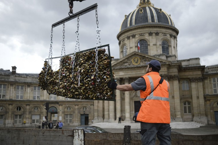 A worker removes 'love padlocks' attached on the railings of the Pont des Arts on June 1, 2015 in Paris. Started by tourists in Paris in 2008, the love locks ritual, which also spread in the early 2000s to cities including New York, Seoul and London, has resulted in the transformation of several bridges : every inch of their railings is now covered with clunky brass padlocks. (AFP Photo/Stephane Sakutinstephane de sakutin)