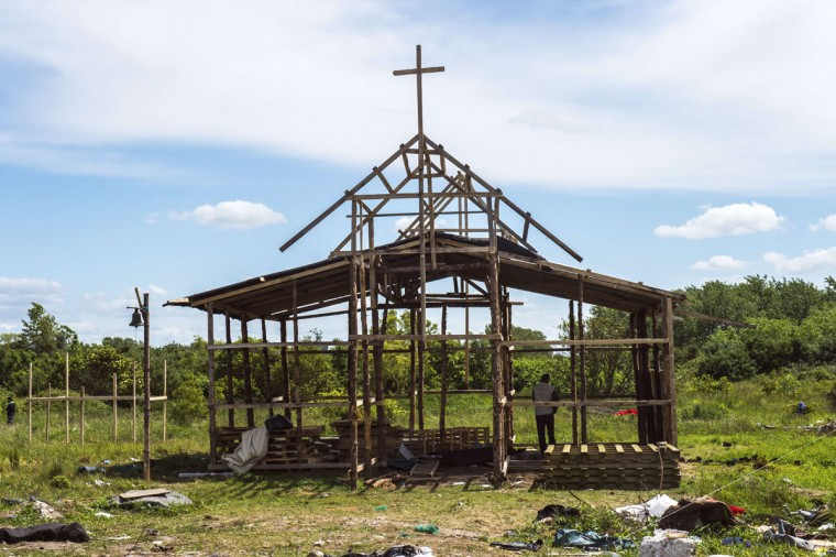 "A man stands in a wooden church under construction at ""the jungle"", a makeshift tent village in Calais, northern France, on June 1, 2015, after a brawl broke out at the camp earlier in the morning. A brawl broke out in the early hours of June 1 between Sudanese and Eritrean migrants in the northern French port of Calais, resulting in 24 injuries, 14 of which required hospital treatment. According to the emergency services, the fight began after a makeshift tent was torched and escalated quickly into running battles with iron bars. (AFP Photo/Philippe Huguen)"