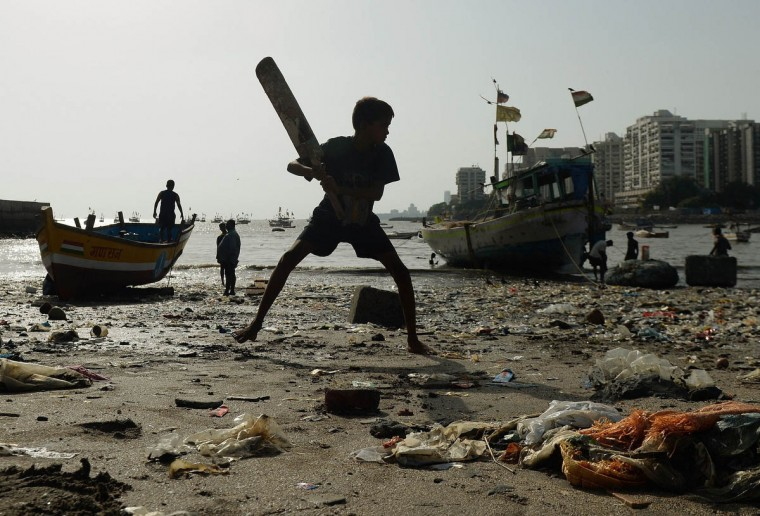 An Indian boy plays cricket on a beach strewn with plastic garbage in Mumbai. (Punit Paranjpe/Getty Images)