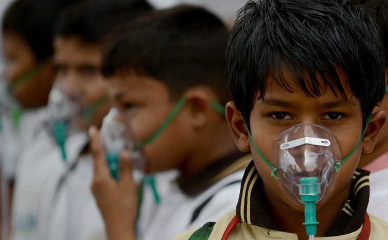 Indian schoolchildren wearing face masks pose for a photograph during before the start of an event to spread awareness of the problem of air pollution in New Delhi on June 4, 2015, on the eve of World Environment Day. The Indian government is under intense pressure to act after the World Health Organization last year declared New Delhi the world's most polluted capital. At least 3,000 people die prematurely every year in the city because of air pollution, according to a joint study by Boston-based Health Effects Institute and Delhi's Energy Resources Institute. World Environment Day is marked annually on June 5. (AFP Photo/Money Sharma )