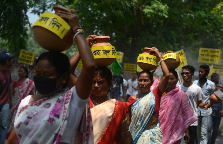 Indian women activists carry water pots during an environment awareness campaign in Siliguri on June 5, 2015, on the occasion of World Environment Day. Social activists, along with school children, took part in the rally to raise awareness of the environment, as well as the use of mosquito nets and fresh drinking water. (AFP Photo/Diptendu Dutta)