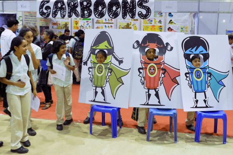 "Visitors to the World Environment Day program organized by the Karnataka Government peek through the photo slot of ""Garb Busters"", the mascot for a litter-free city in Bangalore on June 5, 2015. (Manjunath Kiran/AFP/Getty Images)"