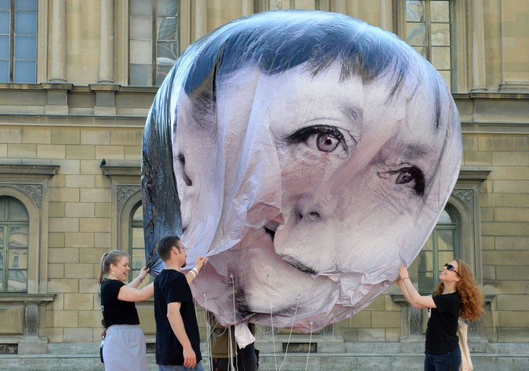 Activists inflate a balloon decorated with the portrait of German Chancellor Angela Merkel on June 5, 2015 in Munich, southern Germany, during a protest activity against the G7 summit. Germany will host the G7 summit at Elmau Castle near Garmisch Partenkirchen, southern Germany, on June 7 and June 8, 2015. (AFP Photo/Christof Stache)