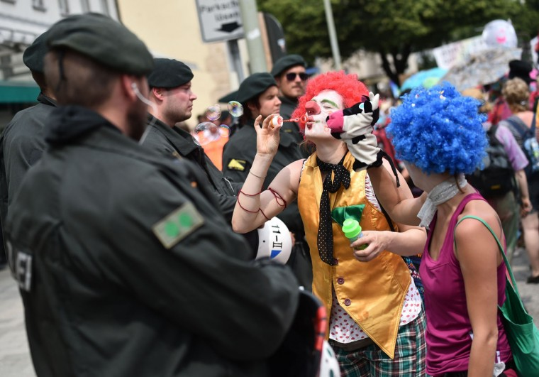 Policer officers watch as an anti G7-protester dressed as a clown blows bubbles in Garmisch-Partenkirchen, southern Germany on June 6, 2015, ahead of the G7 summit. Germany will host the G7 summit at Elmau Castle on June 7 and June 8, 2015. (AFP Photo/Philipp Guelland)