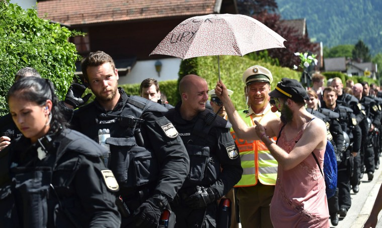 An anti G7-protester protects a policemen from the sun with an umbrella during a rally on a road to Elmau, near in Garmisch-Partenkirchen, southern Germany on June 7, 2015, where to a G7 summit takes place. Germany hosts a G7 summit at the Elmau Castle near Garmisch-Partenkirchen on June 7 and June 8, 2015. (AFP Photo/Philipp Guelland)
