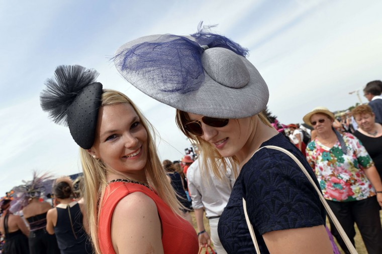Women wearing hats pose as they attend the 166th Prix de Diane, a 2100-metre flat horse race open to three-year-old thoroughbred fillies, on June 14, 2015 in Chantilly, outside Paris. (Miguel Medina/AFP/Getty Images)