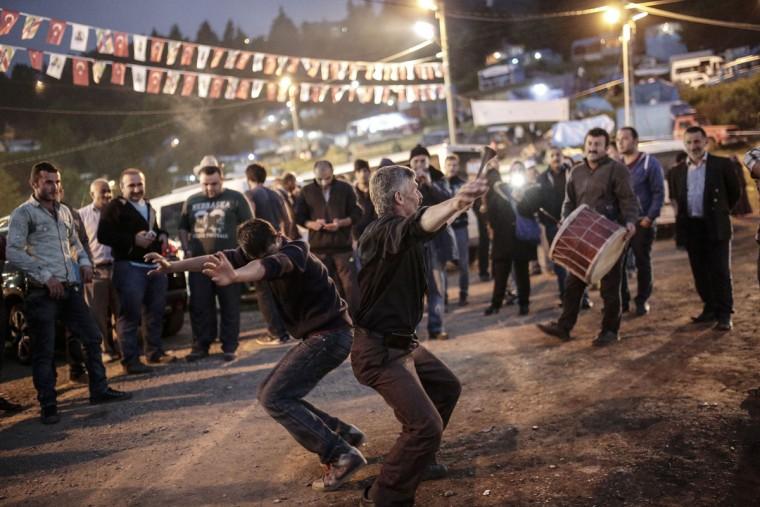 People dance during the traditional Kafkasor Bullfighting festival on June 14, 2015, in Artvin, northeastern Turkey. (YASIN AKGUL/AFP/Getty Images)