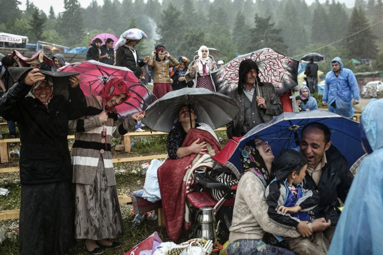 People shelter during rain fall as they watch a bullfight during the traditional Kafkasor Bullfighting festival on June 14, 2015, in Artvin, northeastern Turkey. (YASIN AKGUL/AFP/Getty Images)