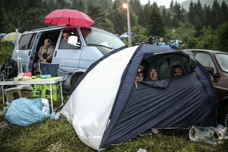 People shelter from rain fall as they watch a bullfight during the traditional Kafkasor Bullfighting festival on June 14, 2015, in Artvin, northeastern Turkey. (YASIN AKGUL/AFP/Getty Images)