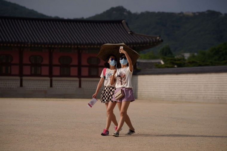 "Two women wearing face masks take a ""selfie"" as they walk in the grounds of Gyeongbokgung palace in Seoul on June 18, 2015. South Korea's ever-growing MERS outbreak has laid bare the country's ill-preparedness against disasters despite President Park Geun-Hye's pledge to overhall public safety measures following last year's ferry disaster, experts say. (ED JONES/AFP/Getty Images)"