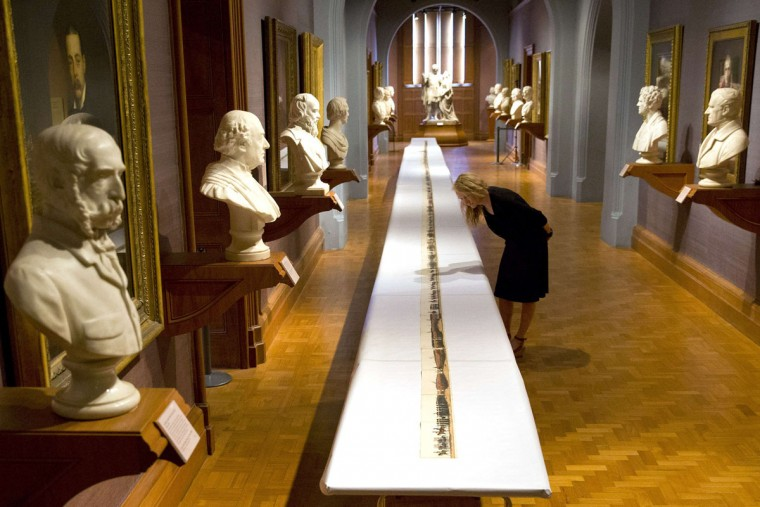 A gallery assistant poses for photographers as she looks at a 67 feet long print showing the complete funeral procession of the Duke of Wellington on the 200th Anniversary of the Battle of Waterloo in London on June 18, 2015. The print by George Augustus Salas was one of many souvenirs to commemorate the event in September 1852. (JUSTIN TALLIS/AFP/Getty Images)