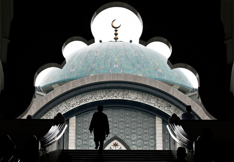 A Malaysian Muslim arrives to offer prayers on the first Friday of the holy Islamic month of Ramadan in Kuala Lumpur on June 19, 2015. Tens of millions across the Muslim world fast from dawn to dusk and strive to be more pious and charitable during the month, which ends with the Eid holiday. (AFP Photo/Manan Vatsyayana)