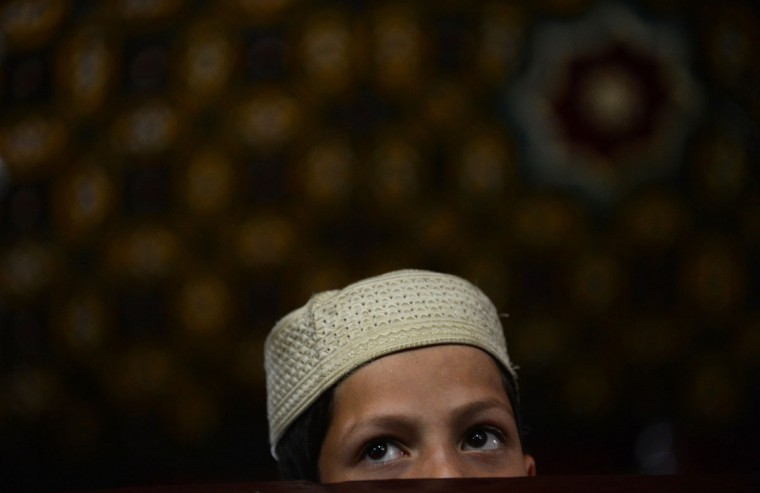 A Kashmiri Muslim boy looks on during the first day of the holy month of Ramadan at the Shah-i-Hamdaan shrine in downtown Srinagar on June 19, 2015. Across the Muslim world, the faithful fast from dawn to dusk, and abstain from eating, drinking, smoking and having sex during that time as they strive to be more pious and charitable. (AFP Photo/Tauseef Mustafa)