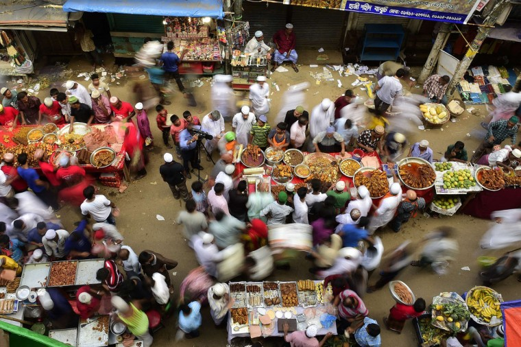 Bangladeshi street vendors prepare Iftar food for breaking the daytime fast on the first day of Ramadan, the holy fasting month of Islam, at a traditional bazaar in the old part of Dhaka on July 19, 2015. Like millions of Muslim around the world, Bangladeshi Muslims celebrate the month of Ramadan by abstaining from eating, drinking, and smoking as well as sexual activities from dawn to dusk. (AFP Photo/P / )
