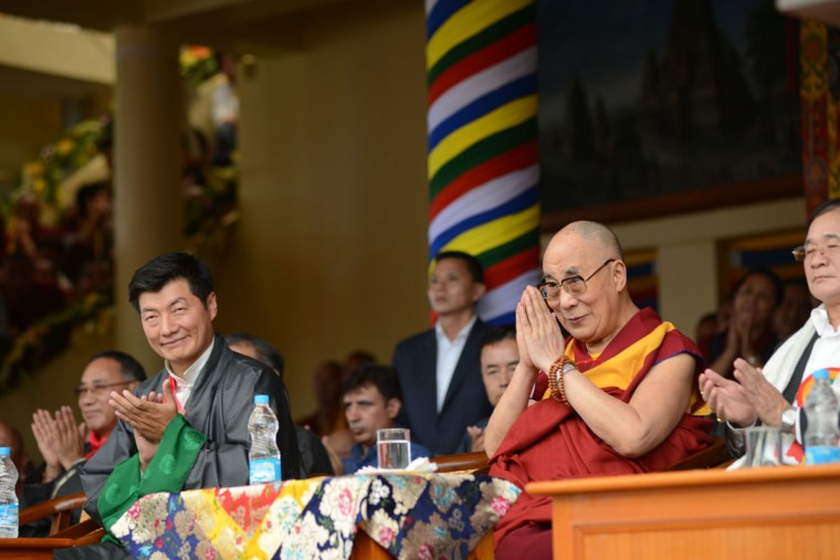 The Dalai Lama (R) greets thousands of his followers at his 80th birthday celebrations at Tsuglakhang temple in McLeod Ganj on 21 June 2015 as Sikyong - Prime Minister of the Central Tibetan Administration -, Lobsang Sangay (L) gestures. The Dalai Lama marked his official 80th birthday on June 21, with prayers and celebrations at his hometown in exile but little to show for decades of lobbying for greater Tibetan autonomy. (AFP Photo/P / )