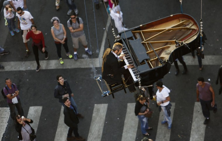 "Brazilian pianist Ricardo de Castro Monteiro performs in the air on a piano hanging from wires during the annual ""Virada Cultural"" event, in Sao Paulo, Brazil, on June 21, 2015. (Miguel Schincariol/AFP/Getty Images)"