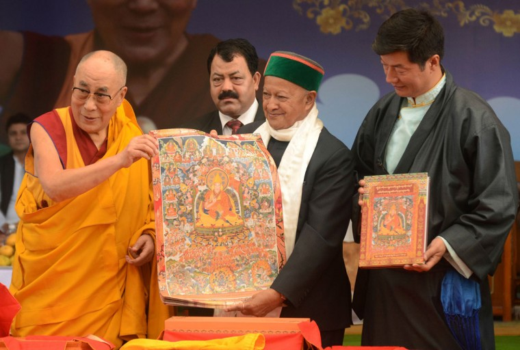 Tibetan Spiritual leader the Dalai Lama (L) is accompanied by The Chief Minister of the northern Indian state of Himachal Pradesh Virbhadra Singh (C) and the leader of the Tibetan government-in-exile, Lobsang Sangay (R) as he releases a Thangka - traditional painting - of his life during an event to celebrate his 80th birthday at Tsuglakhang Temple in McLeod Ganj on June 22, 2015. The Dalai Lama marked his official 80th birthday on June 21, with prayers and celebrations at his hometown in exile but little to show for decades of lobbying for greater Tibetan autonomy. (AFP Photo/Narinder Nanu)