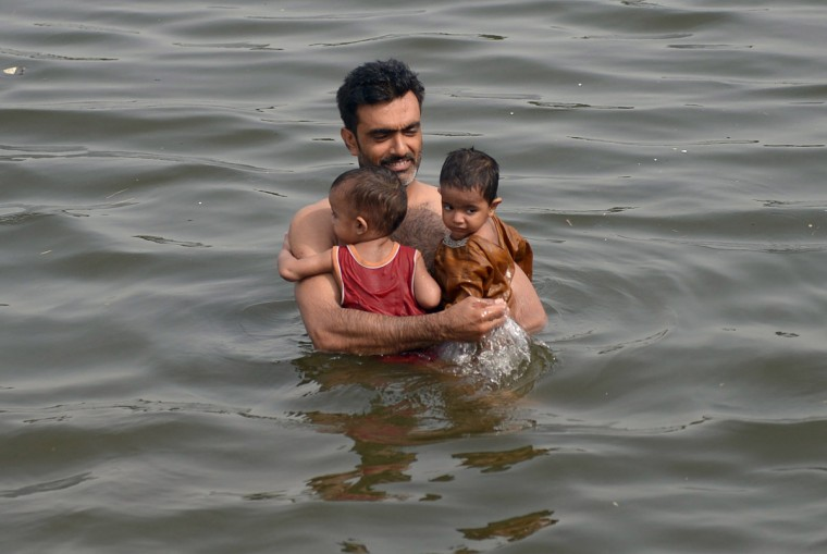 A Pakistani man cool off with his children in the sea during a heatwave in Karachi on June 22, 2015. Nearly 200 people have died in a heatwave in southern Pakistan, officials said, as the government called in the army to help tackle widespread heatstroke in the worst-hit city Karachi. (Rizwan Tabassum/AFP/Getty Images)