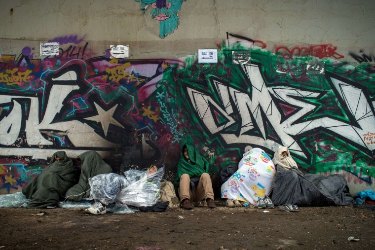 Migrants seek shelter from heavy rain under a bridge in Belgrade on June 24, 2015. (ANDREJ ISAKOVIC/AFP/Getty Images)